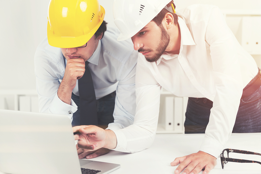 General contractor coordination with architect and construction engineer discussing a project wearing hardhats and looking at a laptop screen.
